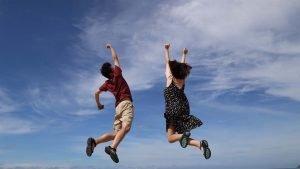 Glade mennesker hopper. Skyer som baggrund.